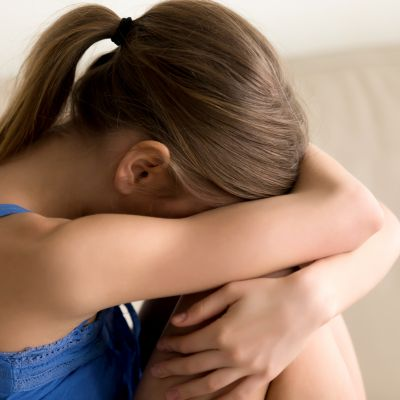 Young frustrated woman hugging knees and crying, suffering from loneliness, feeling stress and fatigue. Stressed offended teenager girl weeping at home alone, nervous because of problems in relations